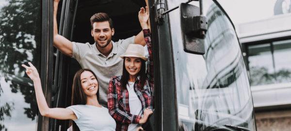 Drei junge Personen stehen im Buseingang und lächeln nach draußen