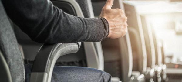 Mann sitzt im Bus und hält Daumen nach oben